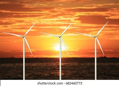 wind turbines in sunset at beach.
