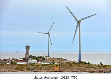 Wind Turbines and village on rocky shores of Aland Islands on sunset. Finland