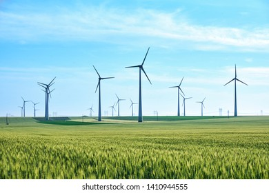 Wind turbines and vivid colors of green wheat field in the Spring on a blue sky, late afternoon. Concept for green energy and a sustainable future.