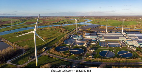 Wind turbines, water treatment and bio energy facility and solar panels in The Netherlands part of sustainable industry in Dutch flat river landscape against blue sky. Aerial circular economy concept.
