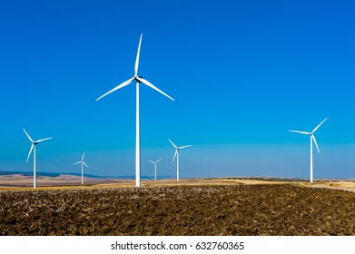 Wind turbines at a windmill farm in a plowed field and a blue sky background.