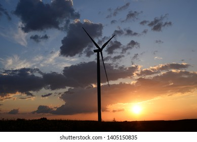 Wind turbines, windmill - power plant on sunny sunset or sunrise near colza field with rural road