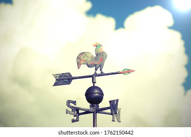 wind vane to indicate the wind direction made of metal with a large rooster above