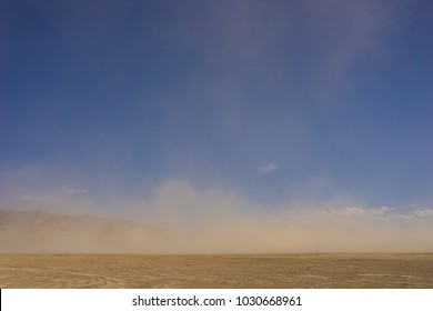 Wind whips sand across the flat Mojave desert in the dry climate of southern California.