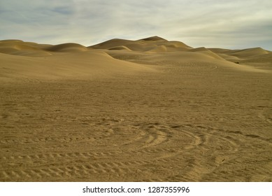 wind-blown sand dune patterns contrast tire tracks left by recreational off-road vehicles