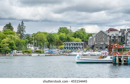 WINDERMERE - MAY 22: Windermere port in Lake district, countryside lake view in England, with cruise boats in Windermere under cloudy blue sky,  on May 22, 2016.