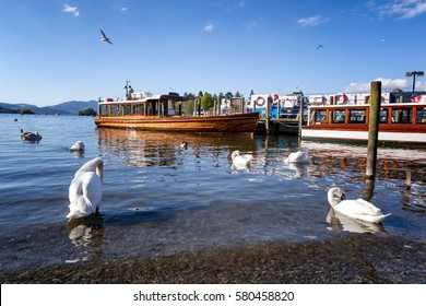 Windermere port in Lake district, countryside lake view in England, with cruise boats in Windermere under  blue sky.