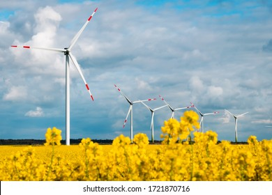 Windfarm in northern Germany surrounded by yellow rapeseed and blue sky
