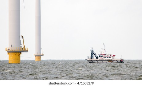 Windfarm service vessel by Windmill park Westermeerwind the largest wind farm in the Netherlands. Urk Netherlands August 2016, Construction of windmill park with boat, offshore windmill farm