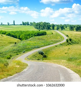 Winding asphalt road among fields in picturesque countryside.