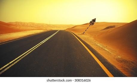 Winding black asphalt road through the sand dunes of Liwa oasis, United Arab Emirates