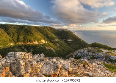 The winding Cabot Trail road seen from high above on the Skyline Trail at sunset in Cape Breton Highlands National Park, Nova Scotia