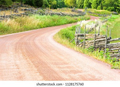 Winding country road with old fashioned Scandinavian roundpole fences on the sides. Location Stensjo in Smaland, Sweden.