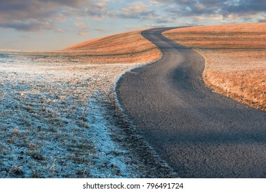 winding country road upon the hill, morning scenery with clouds and hoarfrost at the left side. autumnal background