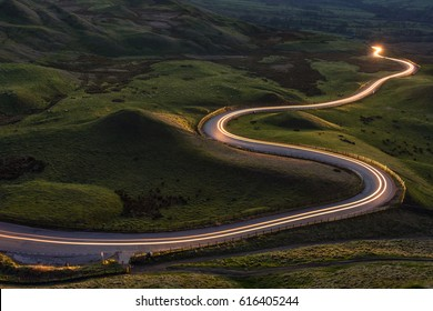 Winding curvy rural road with light trail from headlights leading through British countryside. - Shutterstock ID 616405244