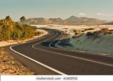 Winding desert road across the dunes of Corralejo, Fuerteventura, in the Canary Islands, Spain.