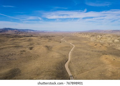 Winding desert road viewed from above the dry ground.
