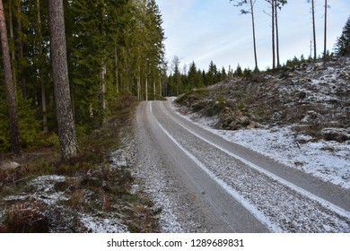 Winding gravel road through the woods in winter season