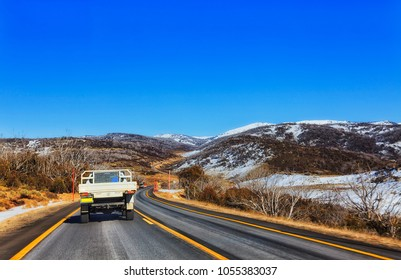 Winding Kosciuszko road leading to Perisher valley town in the middle of snowy mountaisn of Australia - popular winter sports resorts for tourists and ski lovers.