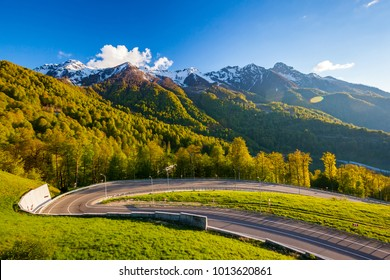 A winding modern asphalt road to the top of a resort in the bright yellow rays of the evening sun, dense forest and the Caucasian mountain range. Summer spring forest mountain landscape, Sochi Russia.