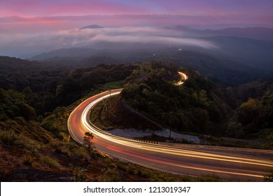The winding mountain road with light tracks from cars at the evening.