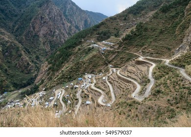 A winding mountain road lined with the houses of a small village.