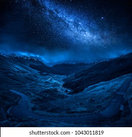 Winding mountain road over a canyon at night with stars