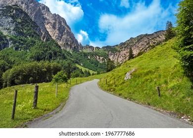 Winding mountain road through green rural alpine landscape with view on Wilder Kaiser, Austrian alps, Austria