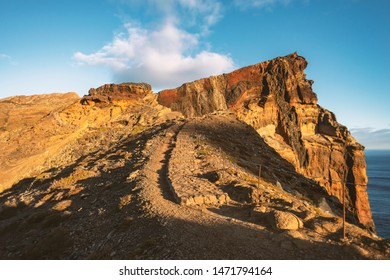 winding mountain trail leading to rocky cliff by sunny morning on Madeira Island