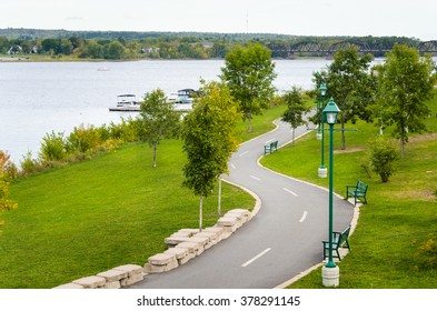 Winding Paved path Through a Riverside Park