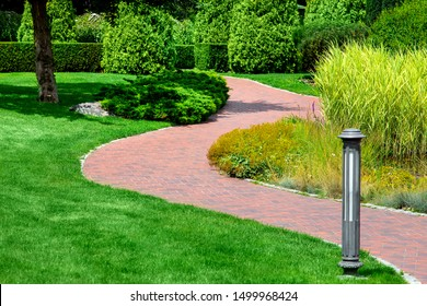 a winding pedestrian walkway made of red paving slabs with a gray stone curb in a park with a green lawn and reeds illuminated by sunlight, a ground street light was installed on the lawn.
