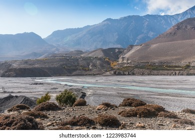 A winding river flows across the dried rocky bed