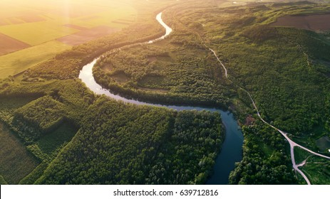 Winding river and green banks shot at sunset from drone