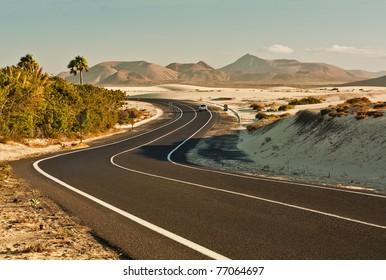 Winding road across the dunes of Corralejo, Fuerteventura, in the Canary Islands, Spain.