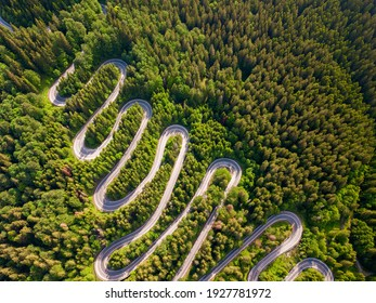 Winding road aerial view by drone. Brasov, Romania. There are huge snow mountains and long winding road in this area. This is a great place to drive and stop during a road trip.