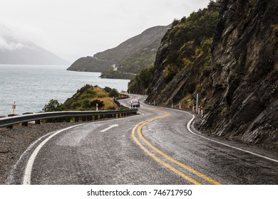 Winding road along the lake Wakatipu leading to Queenstown in New Zealand south island on a rainy day