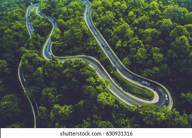 A winding road between tropical forests is visible from the air in North Sumatra, Indonesia.