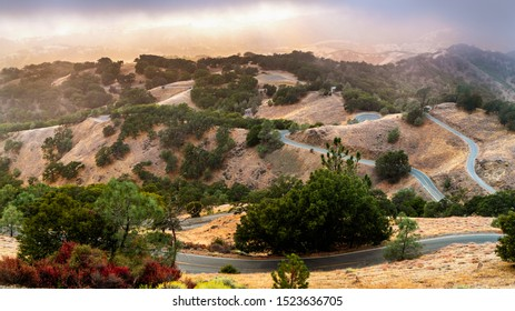 Winding road descending from Mt Hamilton, through rolling hills covered in dry grass and oak trees; sunset light and fog visible in the background; San Jose, south San Francisco bay area, California