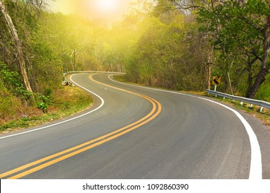 Winding road four lane with yellow line for two way separate direction