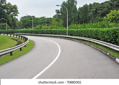 A Winding Road Going Up-Slope With Road Barriers