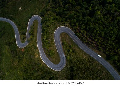 Winding road from the high mountain pass in thailand Great road trip trough the dense woods. Aerial view.