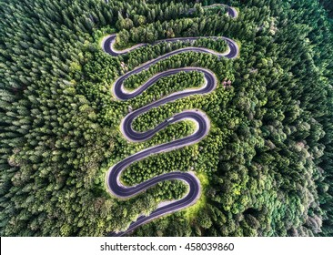 Winding road from the high mountain pass in Transylvania, Romania. Great road trip trough the dense woods. Aerial view.