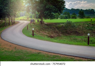 The winding road from the lower right corner leads to the upper left corner and surrounds with lawns and small trees.