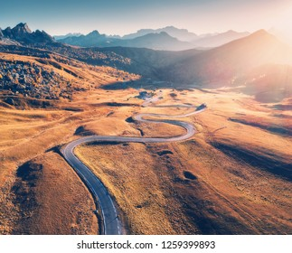 Winding road in mountain valley at sunset in autumn. Aerial view of asphalt road in Passo Giau. Dolomites, Italy. Top view of roadway, mountains, meadows with orange grass, blue sky and gold sunlight