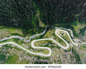 Winding road in the mountains. Forest and river visible, cars passing by. Transfagarasan road in Trasnylvania, Romania, Europe.