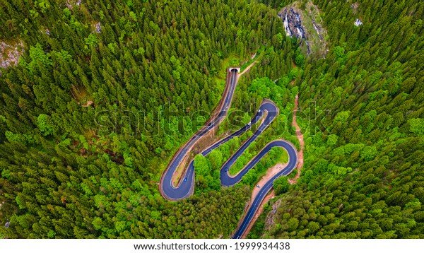 Winding road in the mountains, shot from a drone from a higher altitude and a low camera angle. Photography of a serpentine road in the mountains.