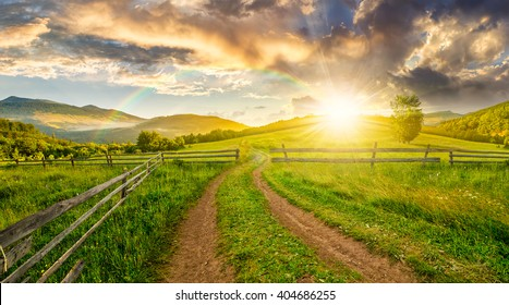 winding road near the wooden fence through the agricultural grassy meadow with lonely tree on hillside in high mountains at sunset