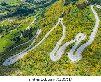 Winding Road on Mountains near Queenstown, New Zealand from aerial view by drone flying over Crown Range Road east of Queenstown in Otago, South Island of New Zealand.