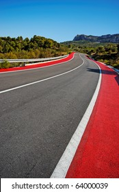 Winding Road and Red Cycle Lane through mountains. Road from Benidorm to Guadalest. Clear blue sky. Converted from RAW