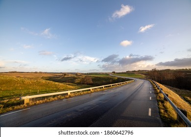 Winding road in a rural rolling hill landscape with side light from the morning sun. Clear sky with clouds at horizon in a wide angle scene.